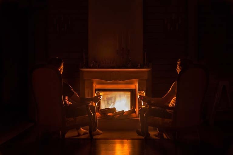 2 person holding a wine glass is near at the fireplace