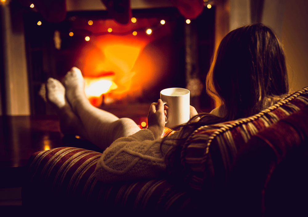 woman with feet up in front of the wood burning types of fireplaces